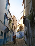 Old Woman Walking in Streets of the Typical Blue Colored Houses in the City.  (Chefchaouen, Morocco)